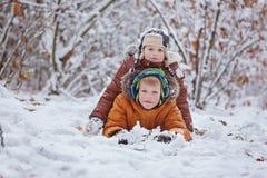 2 маленьких дет, братья мальчика играя и лежа в снеге outdoors во время снежностей Активный отдых с детьми в зиме на co Стоковые Изображения RF