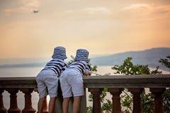 2 маленьких дет, братья мальчика, смотря самолет i посадки Стоковая Фотография