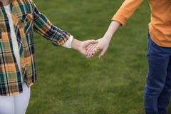 2 маленьких дет держа руки пока стоящ на зеленой траве Стоковая Фотография RF