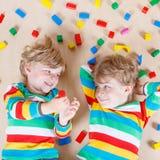 2 маленьких дет играя с красочными деревянными блоками крытыми Стоковое фото RF