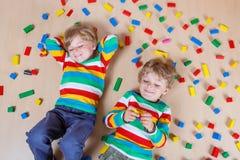 2 маленьких дет играя с красочными деревянными блоками крытыми Стоковые Фотографии RF