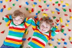 2 маленьких дет играя с красочными деревянными блоками крытыми Стоковые Изображения RF