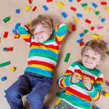 2 маленьких дет играя с красочными деревянными блоками крытыми Стоковое Фото