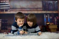 2 маленьких дет, мальчики, читая книгу с лупой Стоковые Фото
