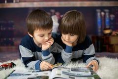 2 маленьких дет, мальчики, читая книгу с лупой Стоковые Изображения
