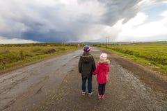 2 маленьких дет мальчик и девушка идя на дорогу Стоковое Изображение