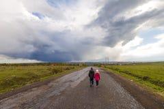 2 маленьких дет мальчик и девушка идя на дорогу Стоковые Изображения