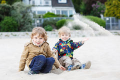 2 маленьких дет сидя на пляже реки Эльбы и играя t Стоковые Фото