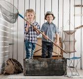 2 маленьких дет стоя в комоде с сетью в руках Стоковое фото RF