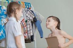 2 маленьких дет стоя около вешалки с одеждами дома Стоковые Изображения