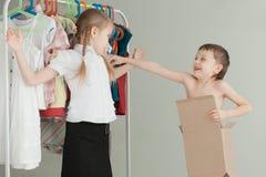 2 маленьких дет стоя около вешалки с одеждами дома Стоковое Фото