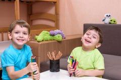 2 маленьких кавказских друз играя с сериями красочных пластичных блоков крытых Активные мальчики ребенк, отпрыски имеющ строить п Стоковое Изображение