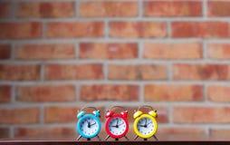 3 маленьких красных будильника на таблице Стоковое Изображение