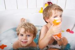 2 маленьких мальчика близнецов имея потеху с водой путем принимать ванну в ба Стоковая Фотография RF