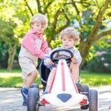2 маленьких мальчика отпрыска играя с автомобилем педали в саде дома Стоковые Фотографии RF