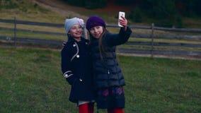 2 маленьких милых девушки делают selfie на сотовом телефоне outdoors сток-видео