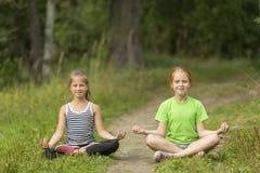 2 маленьких милых девушки сидя в положении лотоса в парке Стоковые Изображения
