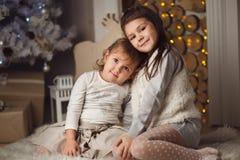 2 маленьких милых девушки сидя около рождественской елки и камина Стоковые Фотографии RF