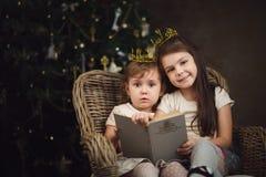 2 маленьких милых девушки сидя около рождественской елки и читая bo Стоковые Фотографии RF