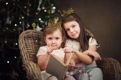 2 маленьких милых девушки сидя около рождественской елки и читая bo Стоковое Изображение