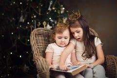 2 маленьких милых девушки сидя около рождественской елки и читая bo Стоковое фото RF