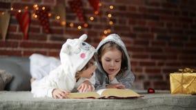 2 маленьких милых отпрыска читая книгу в кровати около рождественской елки с светами и освещением семья счастливые 2 видеоматериал