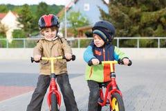 2 маленьких отпрыска имея потеху на велосипедах в городе на каникулах Стоковое Фото