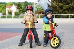 2 маленьких отпрыска имея потеху на велосипедах в городе на каникулах Стоковая Фотография