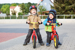2 маленьких отпрыска имея потеху на велосипедах в городе на каникулах Стоковая Фотография RF