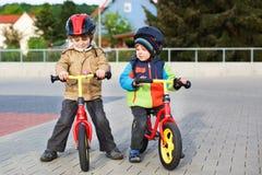 2 маленьких отпрыска имея потеху на велосипедах в городе на каникулах Стоковые Изображения