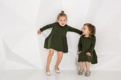 2 маленьких подруги в таких же темных ых-зелен платьях представляя в студии с белыми стенами Стоковые Фото