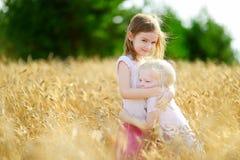 2 маленьких сестры в пшеничном поле на летний день Стоковые Изображения