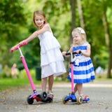 2 маленьких сестры ехать их самокаты Стоковое Изображение