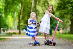 2 маленьких сестры ехать их самокаты Стоковые Фотографии RF