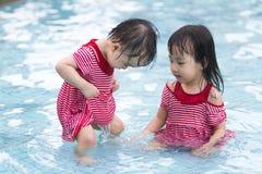 2 маленьких сестры играя в воде Стоковое Изображение RF