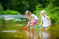 2 маленьких сестры играя с бумажными шлюпками Стоковые Изображения RF