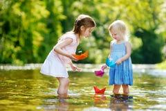 2 маленьких сестры играя с бумажными шлюпками Стоковые Фото