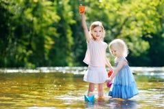 2 маленьких сестры играя с бумажными шлюпками Стоковое фото RF