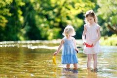 2 маленьких сестры играя с бумажными шлюпками Стоковая Фотография RF