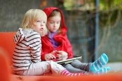 2 маленьких сестры играя с цифровой таблеткой Стоковая Фотография RF