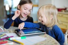 2 маленьких сестры играя с цифровой таблеткой Стоковая Фотография