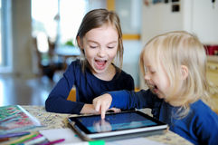 2 маленьких сестры играя с цифровой таблеткой Стоковые Фотографии RF