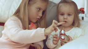 2 маленьких сестры играя с шариками рождества пока сидящ на кресле Стоковое Изображение