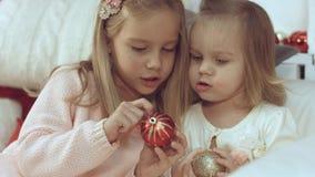 2 маленьких сестры играя с шариками рождества пока сидящ на кресле Стоковая Фотография