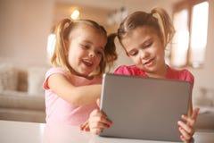 2 маленьких сестры используя таблетку Стоковые Фото