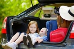 2 маленьких сестры идя к каникулам автомобиля Стоковое фото RF