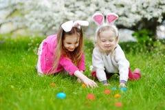 2 маленьких сестры охотясь для пасхального яйца на день пасхи Стоковое фото RF