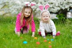 2 маленьких сестры охотясь для пасхального яйца на день пасхи Стоковые Фотографии RF