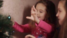 2 маленьких сестры украшая рождественскую елку с ель-конусом год подготовки 2008 ингридиентов новый Счастливые девушки и семья видеоматериал