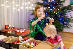 2 маленьких сестры украшая рождественскую елку Стоковые Изображения